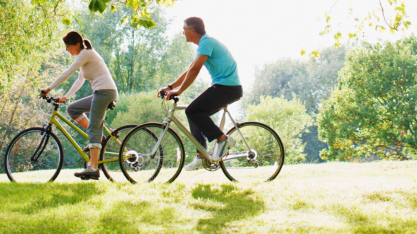 Man and woman riding bikes in park