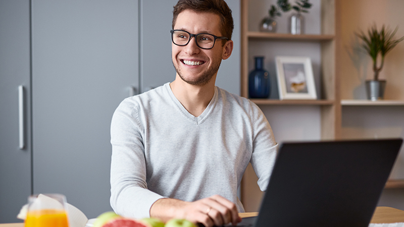 Man in front of laptop smiling
