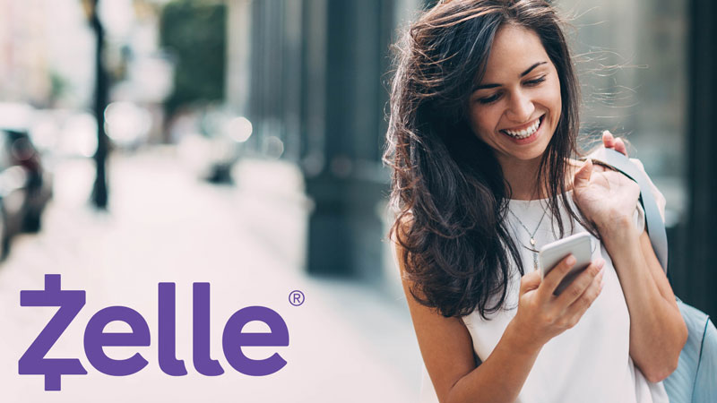 mujer usando Zelle en un teléfono móvil para enviar dinero