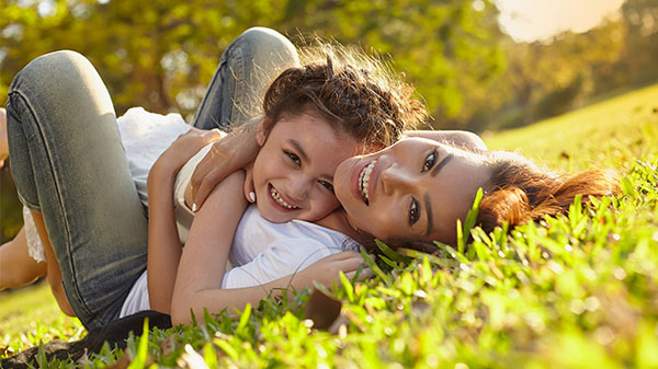 mother and daughter laying in the grass