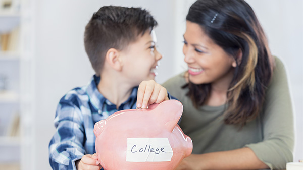 mom smiling at son as he drops change into a piggy bank