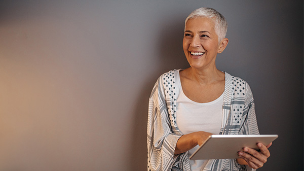 older woman using a tablet and smiling