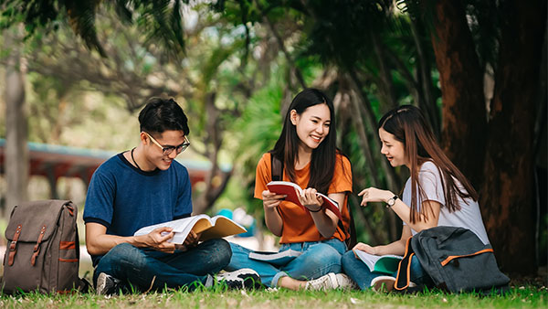 three asian friends studying in the park
