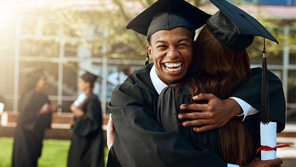 estudiante afroamericano sonriente con toga de graduación abrazando a una compañera