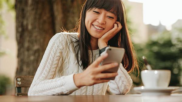 mujer asiática joven en un café mirando su teléfono