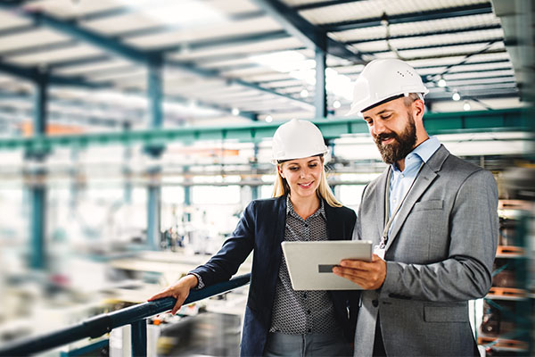 man and woman wearing white hard hats looking at a tablet