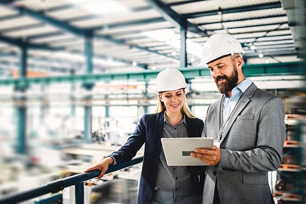 hombre y mujer con cascos blancos mirando una tablet