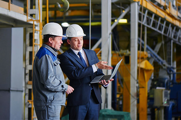 two men in white hard hats looking at a tablet