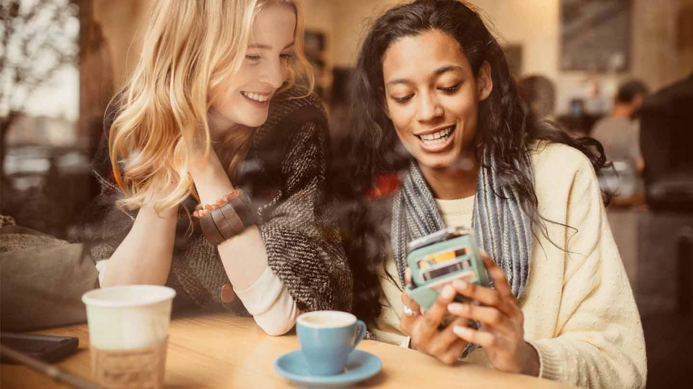 dos muchachas en una cafetería mirando un teléfono