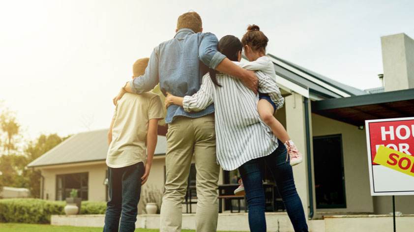 Family hugging as they look at sold home