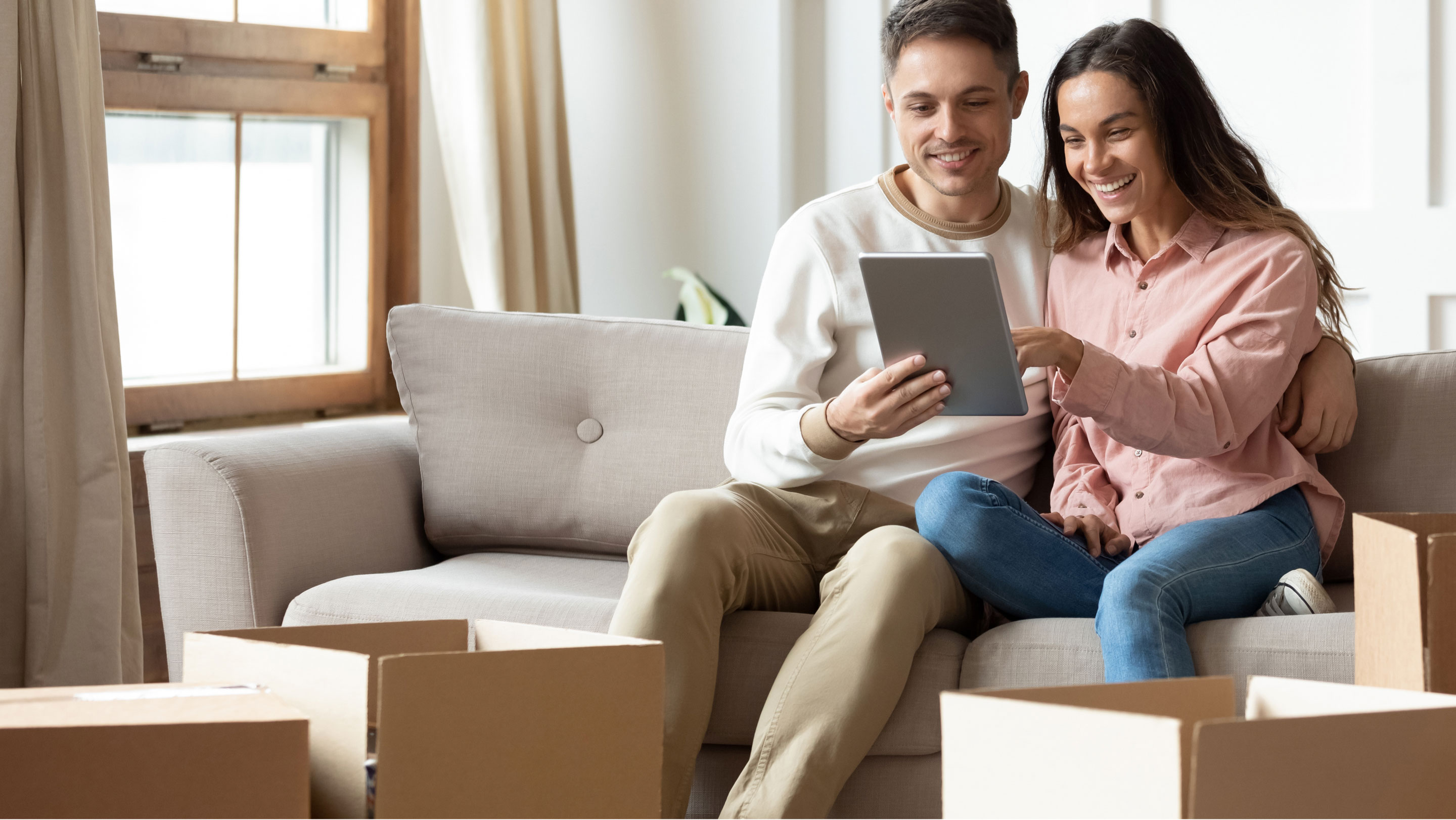 Couple sitting on couch pointing at tablet screen