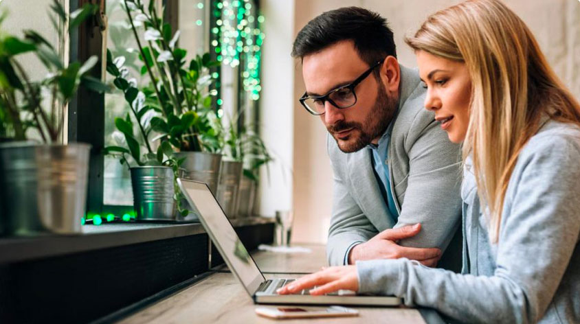 Couple sitting at counter looking at laptop screen