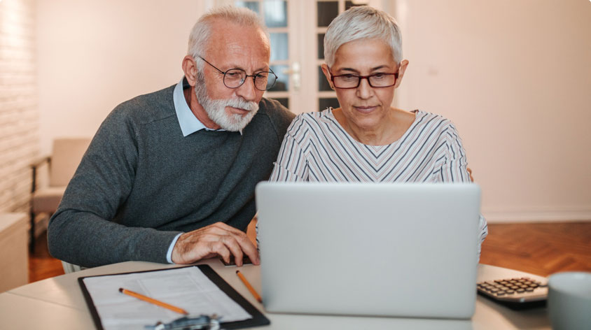 Older couple looking at laptop screen