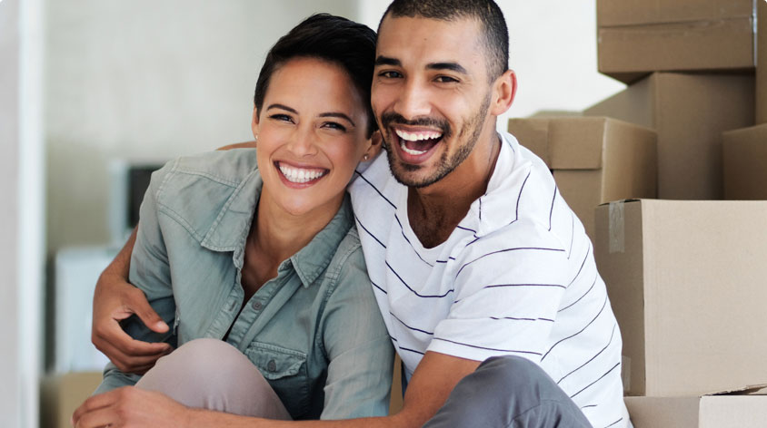 Smiling couple sitting in room with unpacked boxes