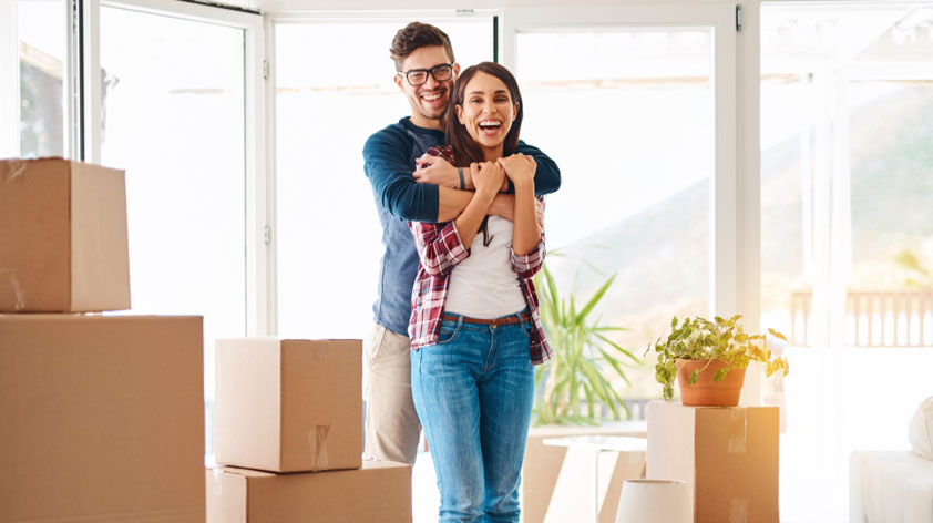 Pareja abrazada y con entusiasmo por su casa nueva