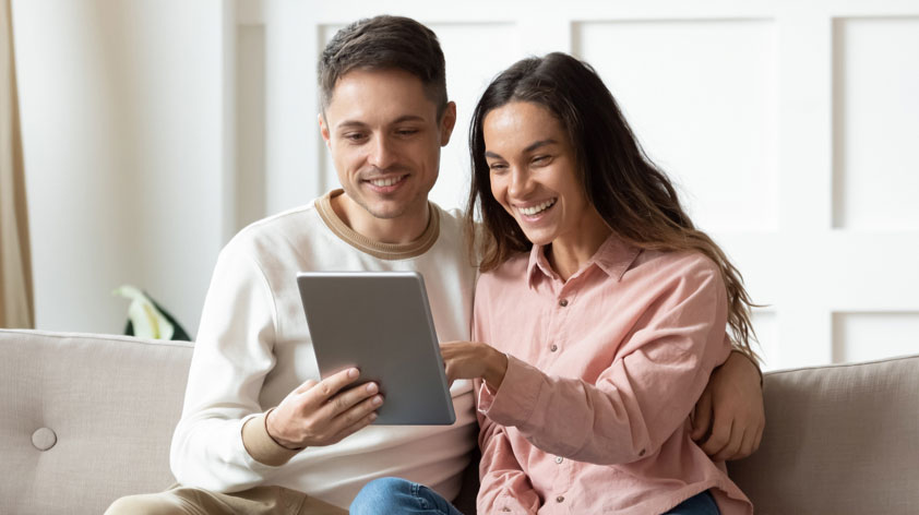 Couple smiling and looking at tablet screen