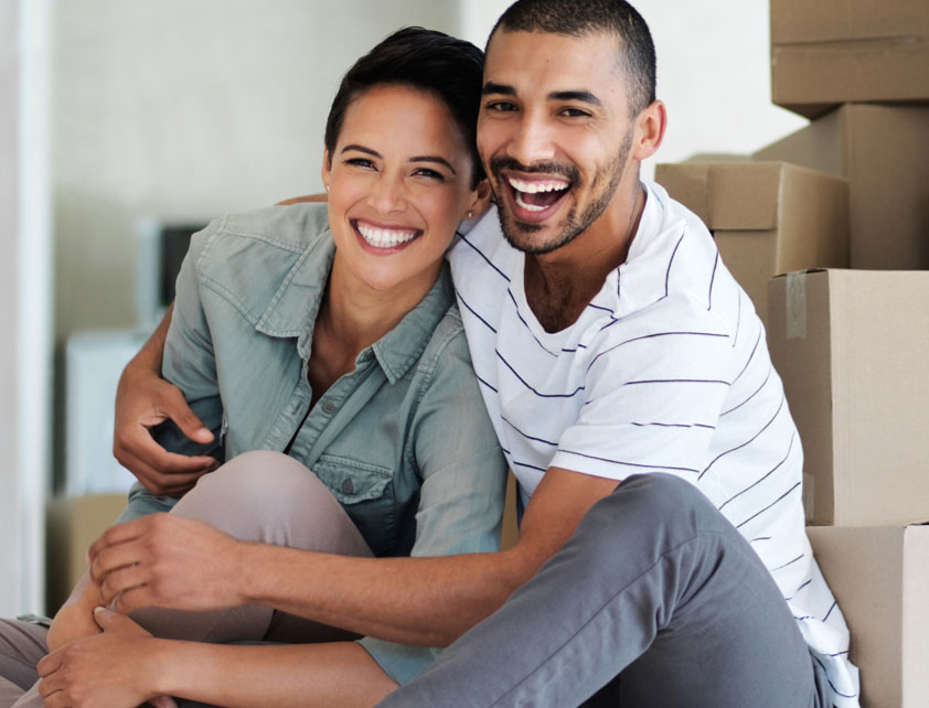 Couple hugging in room full of packed boxes