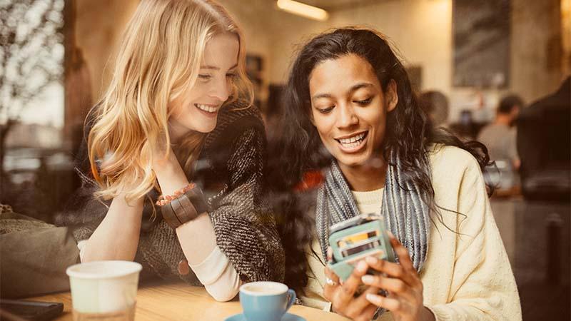 dos mujeres en una cafetería mirando un teléfono