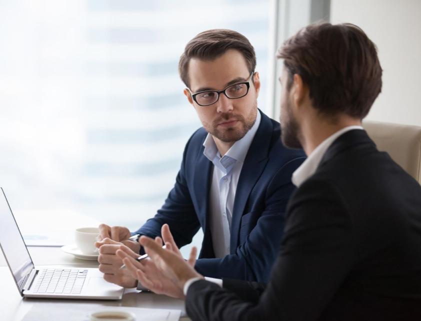 Dos hombres hablando frente a una laptop
