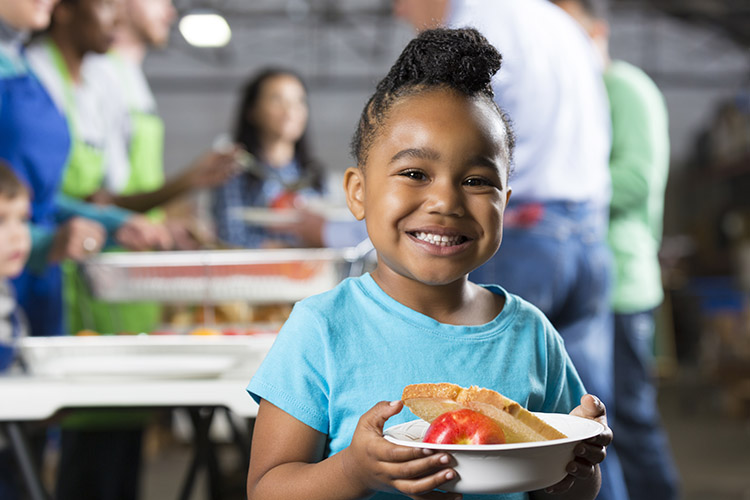 niña pequeña sonriente sosteniendo un tazón de comida en un banco de alimentos