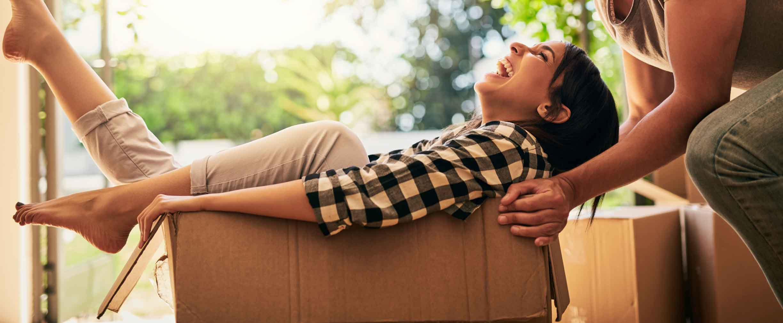 una pareja joven feliz desempacando cajas en su nueva casa