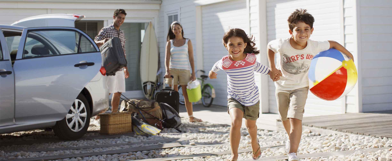 familia joven saliendo del auto en su vivienda sobre la playa