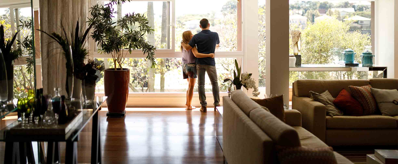 pareja abrazada en su sala mirando por la ventana