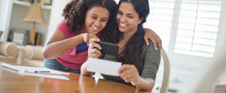 hija ayudando a su madre a depositar un cheque a través de un smartphone