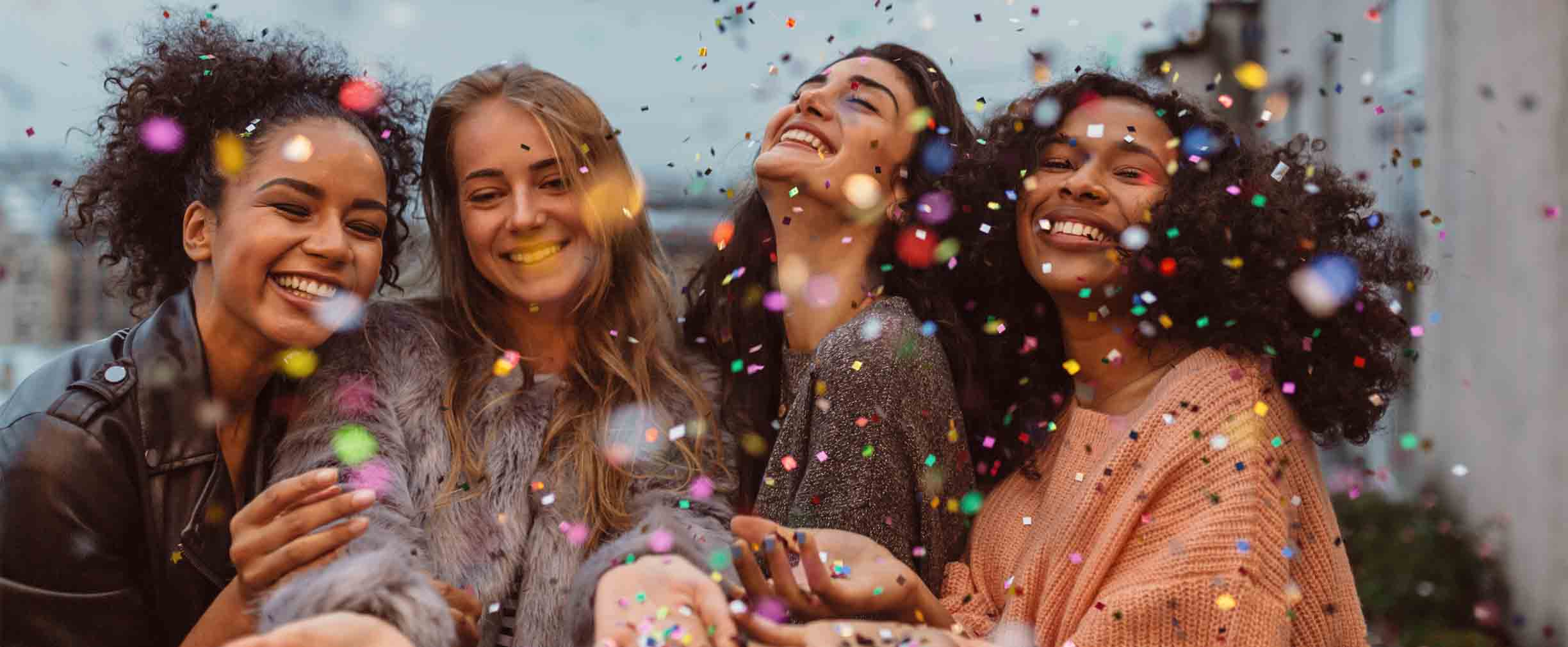 four girls celebrating with confetti