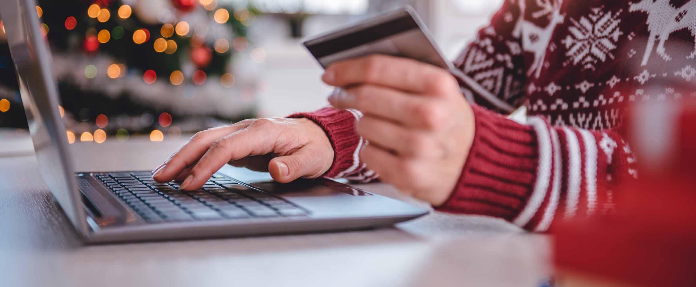 mujer con tarjeta de crédito en la mano comprando por Internet durante las fiestas