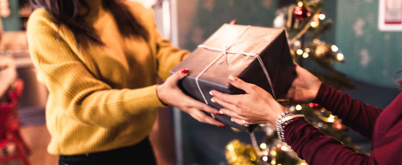 mujer joven recibiendo un regalo de Navidad de un amigo