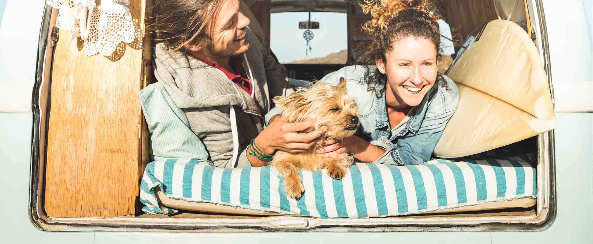 two women and a dog traveling in a van