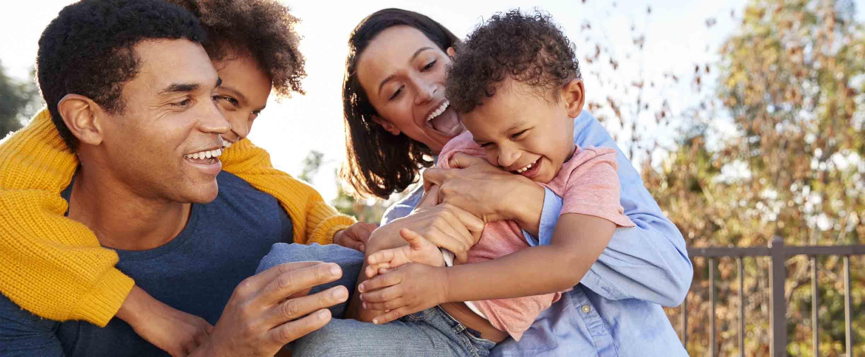 Padres jóvenes de raza mixta jugando al aire libre y llevando a sus niños al jardín