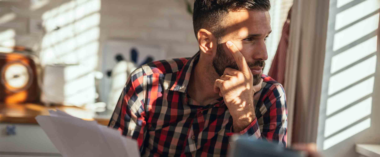 Hombre estresado sentado en la cocina con papeles en la mano