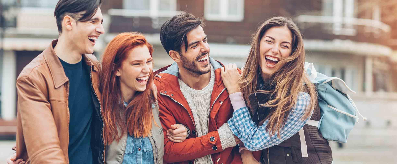 cuatro estudiantes caminan juntos y ríen