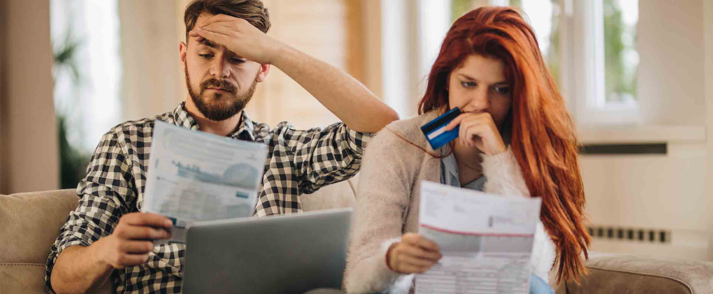 Worried couple feeling frustrated while holding a credit card and looking at a computer and bills