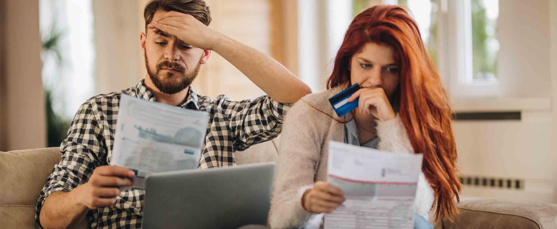 Pareja preocupada y frustrada frente a una computadora y mirando facturas, con una tarjeta de crédito en la mano