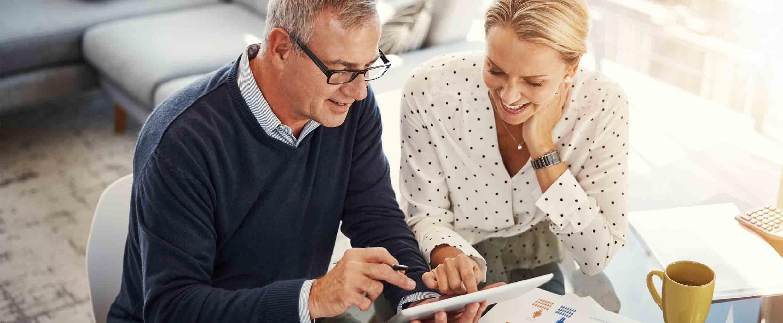 pareja adulta revisando sus finanzas en una tableta