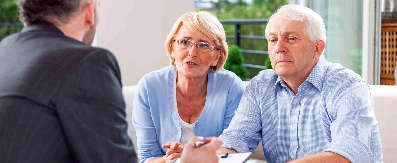 una pareja discutiendo estrategias de retiro al momento de la jubilación con un asesor financiero