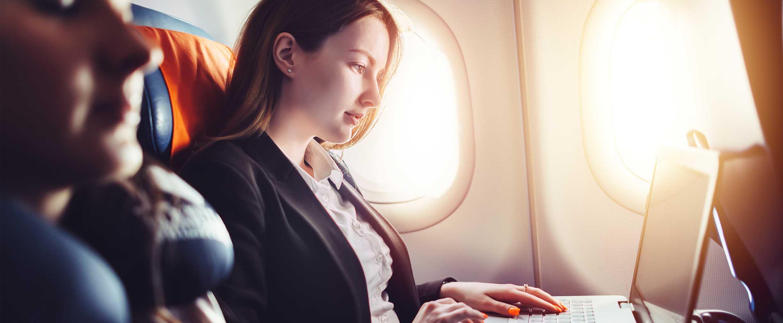 viajero de negocios trabajando en una laptop durante un vuelo
