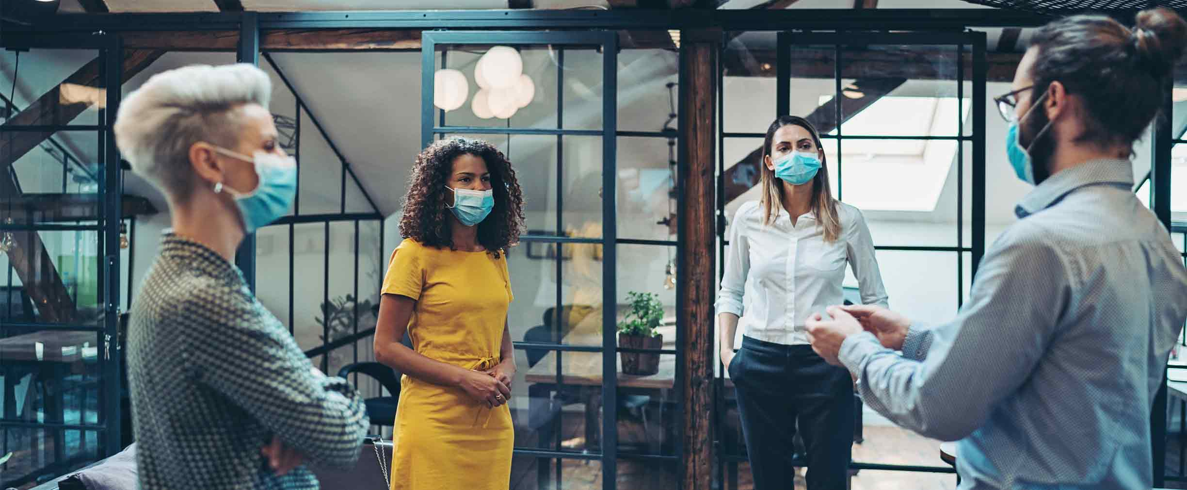 Business persons with protective masks meet in a co-working area