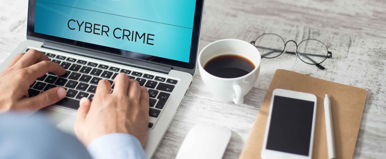 persona de negocios usandouna laptop y una advertencia de fraude en la pantalla