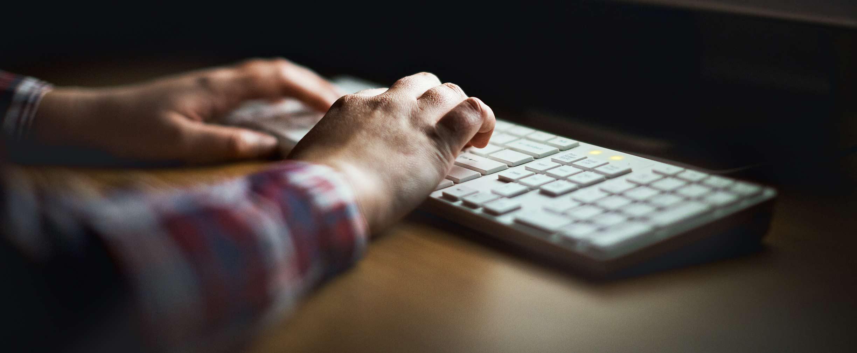 Manos que escriben en teclado de computadora iluminado por el monitor