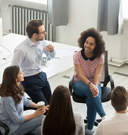 Discusión grupal, empleados hablando en círculo.