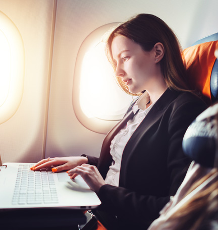 business traveler working on laptop during flight