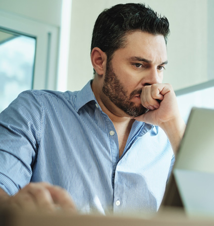Empresario preocupado que observa una laptop