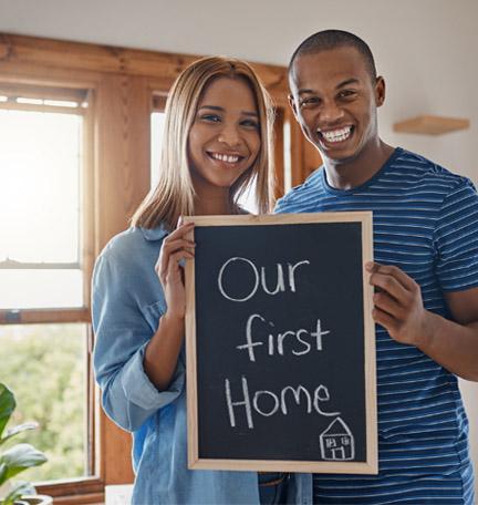 pareja feliz sonriente sosteniendo un cartel que dice nuestra primera casa