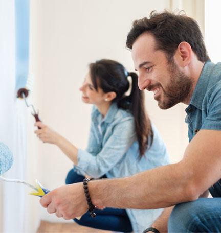 pareja joven pintando las paredes de su casa