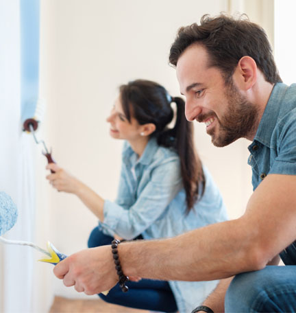 young couple painting the walls of their home