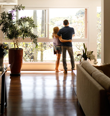 couple hugging in their living room looking out the window